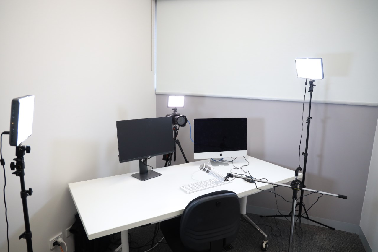 a photo of a desk with three lights and two computer monitors