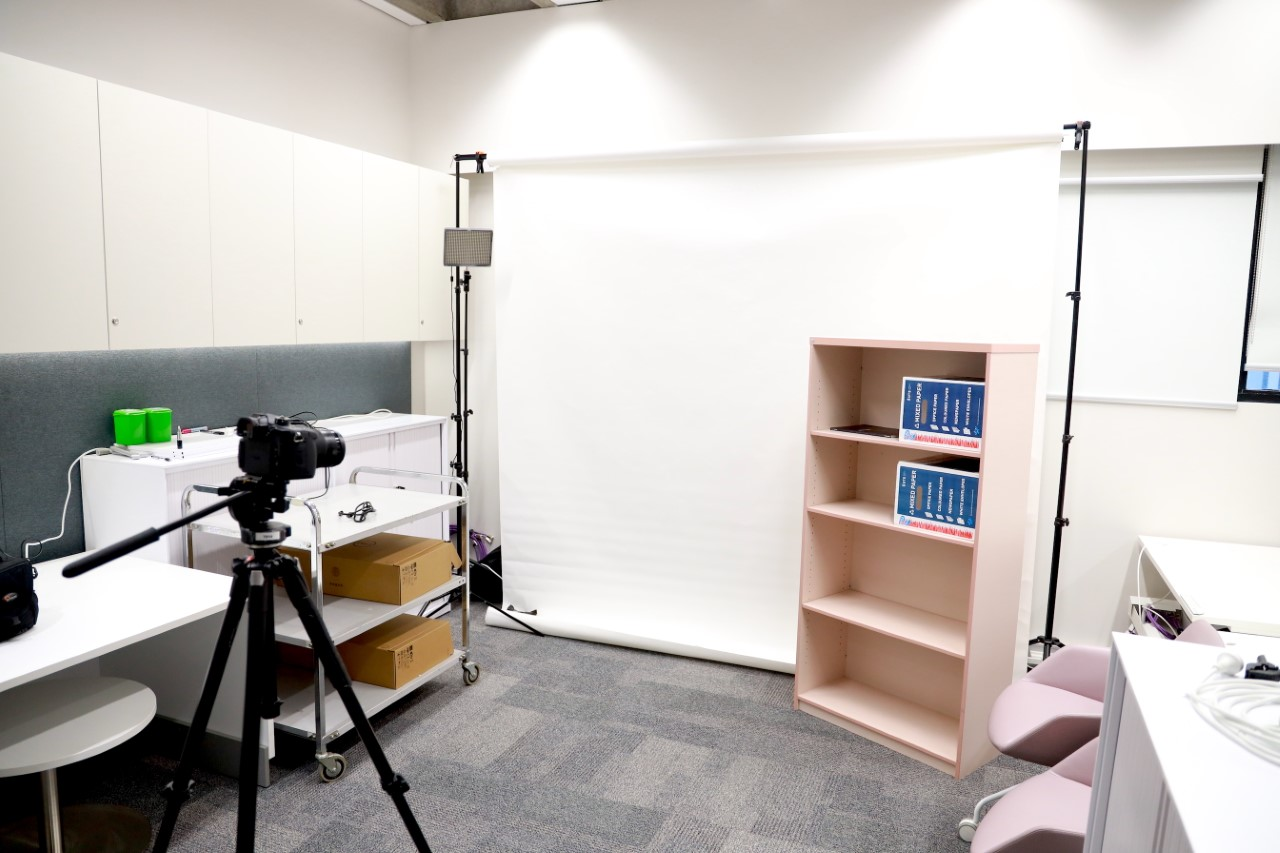 a photo of a room with a white backdrop, lighting set up and video camera on tripod