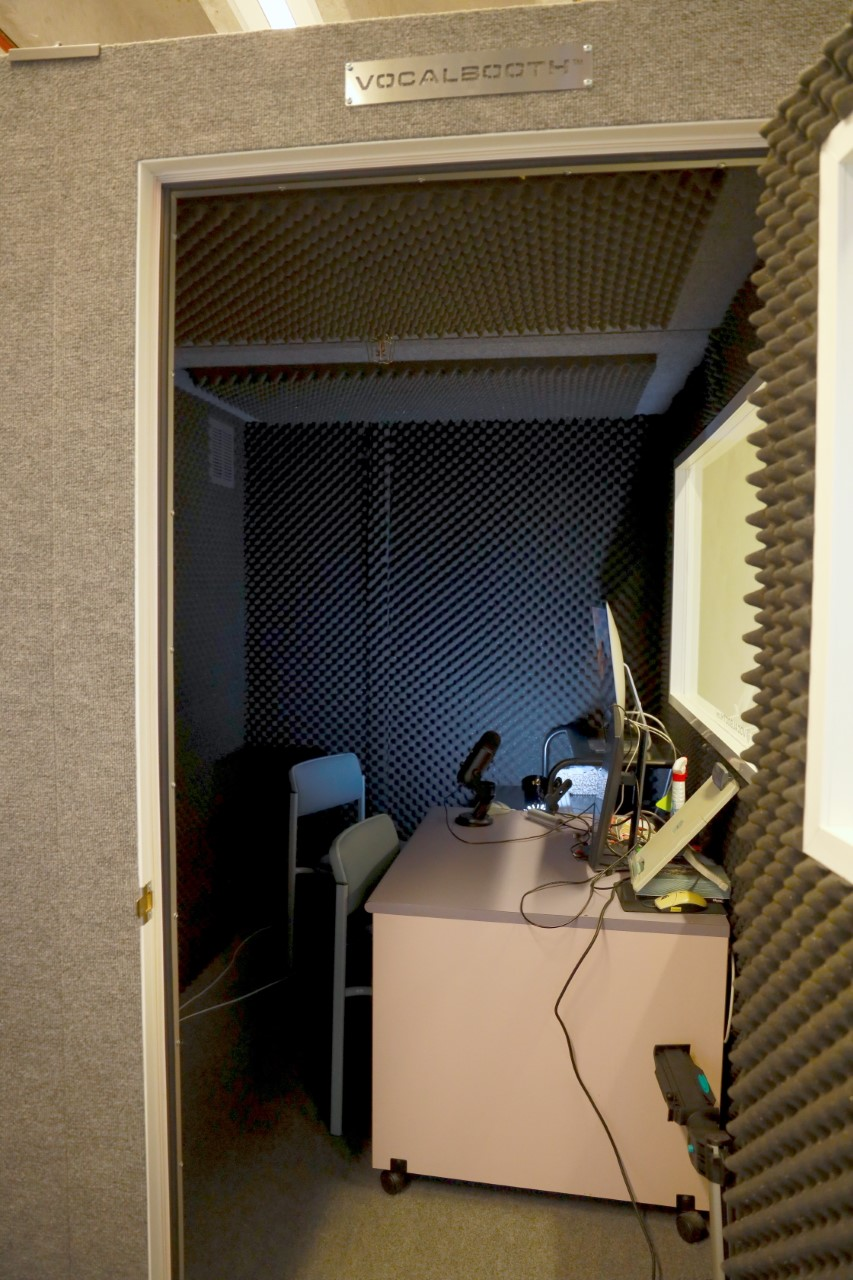 a photo of the sound recording booth - a small room with a computer, mic and insulated walls