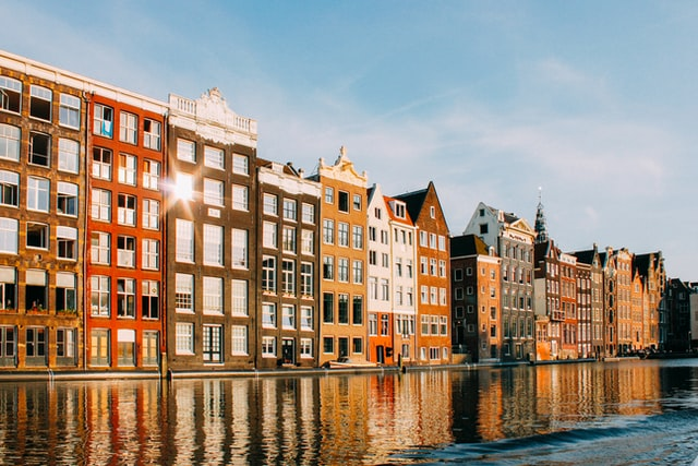 a canal in Amsterdam lined with traditional, colourful Dutch houses